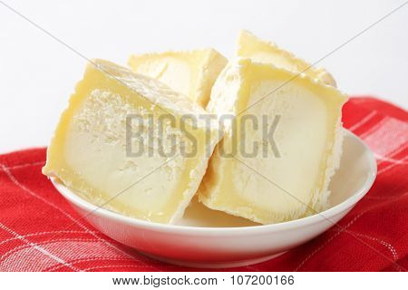 detail of sliced soft white rind cheese in white bowl