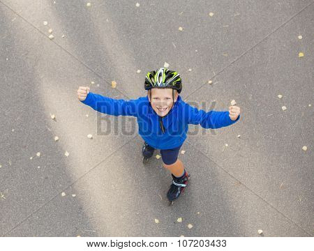 Happy boy on roller skates showing hands up