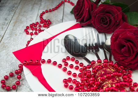 Table setting with red roses on white wood background