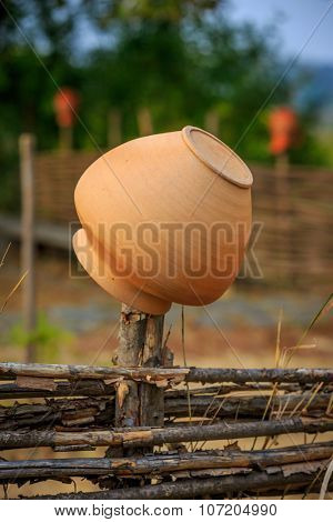 Traditional Ukrainian clay jug on wooden fence
