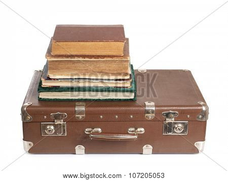 Old suitcase and a book on white background