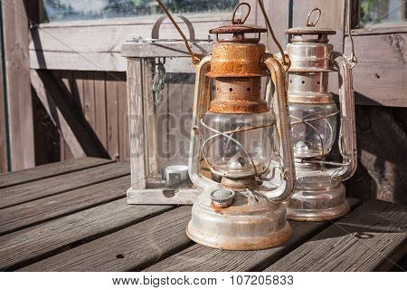 Rusted Kerosene Lamps Stands On Old Wooden Table