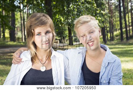 Winking Boy And Unsure Girl Sitting On The Green Grass In Nature Sunny Day.