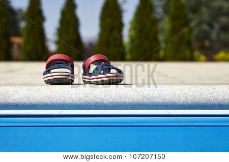 Baby Sandals At The Edge Of Swimming Pool