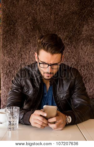 Handsome Businessman With Modern Haircut Looking At Smartphone