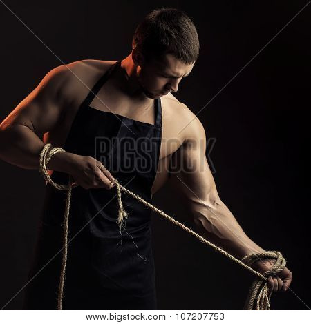 Muscular Man In Apron With Rope