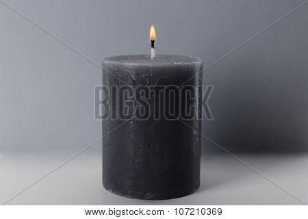 Alight wax grey candle on light background