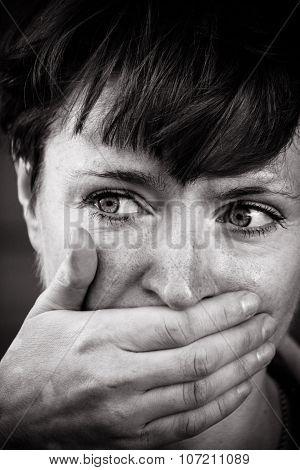 The girl's face close up, mouth and nose with his hand trapped in the eyes of fear.