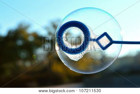 A soap bubble is inflated against background of the autumn landscape and blue sky