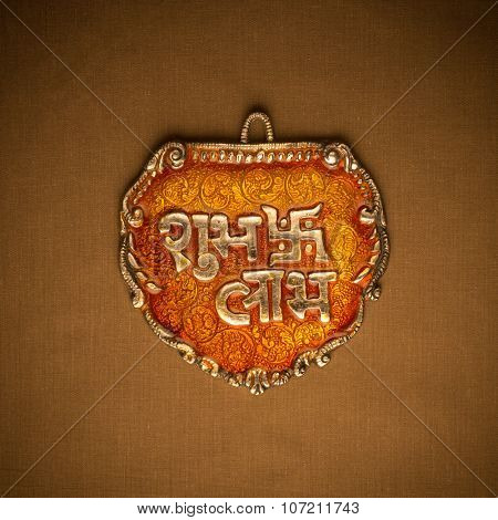 'Shubh Labh' religious slogan written on metal plaque. Translation: 'Auspiciousness and Profit'. Indian religious object.