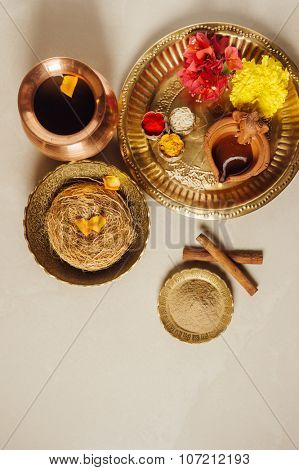 Abhynga snana - an Indian way of having bath with Ayurvedic herbal powder on a special religious events. Puja thali with herbal ingredient still life from above.