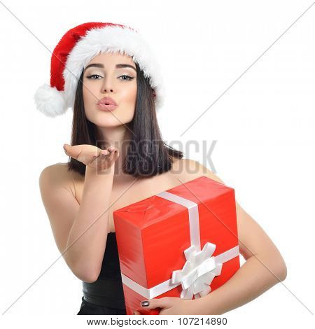 Christmas girl. Beautiful x-mas woman holding gift box and sending wind kiss over white background.