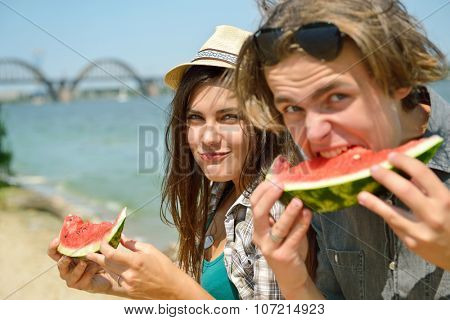 Happy friends eating watermelon on the beach. Youth lifestyle. Happiness, joy, friendship, holiday, beach, summer concept. Group of young people having fun outdoor.