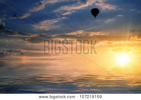 natural landscape with cloudy sky at sunset and air balloon reflected in water