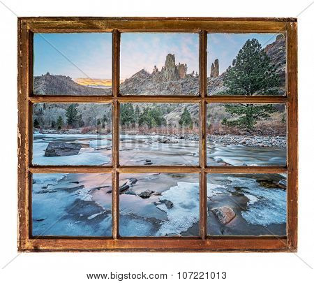 travel concept  or a greeting card from Colorado - Poudre River in winter as seen  through vintage, grunge, sash window with dirty glass