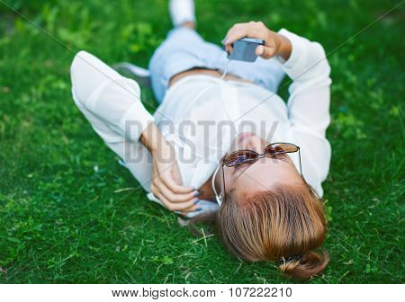 Young Woman Touching Cell Phone And Lying On Meadow
