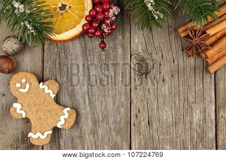 Christmas gingerbread man on wooden background with tree branch border