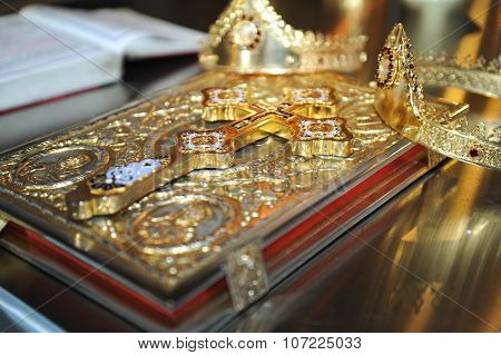 crosses , rings and crowns of gold on the table in church.Wedding celebration