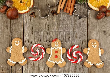 Christmas gingerbread cookies, peppermints and baking goods on rustic wood