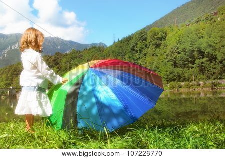 Little Child Plays With Her Colored Umbrella Near The Lake