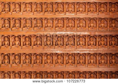 Background Of Carved Wall With Many Buddha Figures Sitting In Yoga Position.