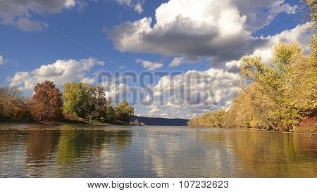 River Shoreline Landscape. Autumn or Fall Foliage. Blue Sky with Clouds.