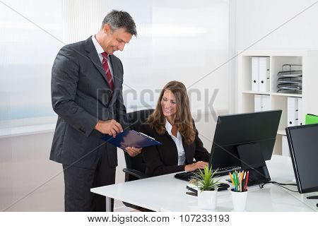 Businessman Showing Report To Female Employee