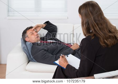 Patient Relaxing On Couch In Front Of A Psychiatrist