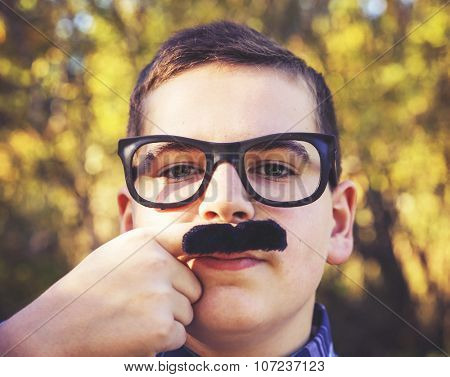 a young boy holding a finger mustache up to his face wearing a pair of urban hipster glasses and making a serious face in a sunny outdoor setting toned with a retro vintage instagram filter app