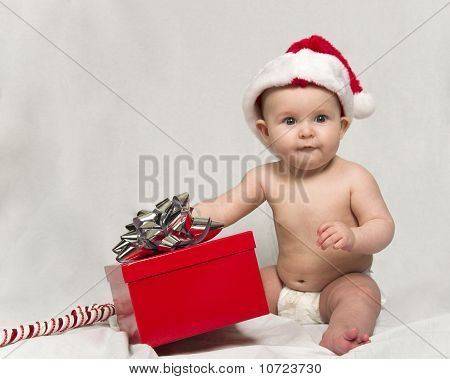 Baby Wearing Santa hat with Christmas Present