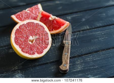 Fresh Sliced Grapefruit On A Dark Wooden Surface