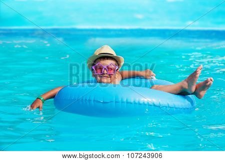 Cute boy wearing hat, glasses in inflatable ring