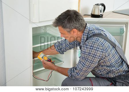 Technician Checking Fridge With Digital Multimeter