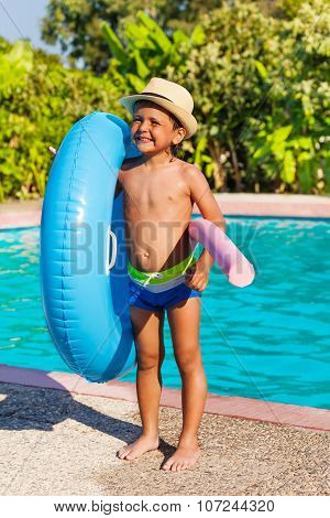 Boy in hat holding inflatable ring and pool noodle