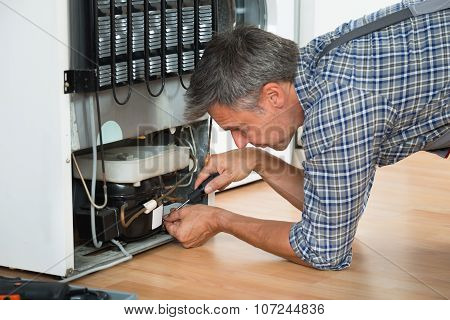 Serviceman Working On Fridge At Home