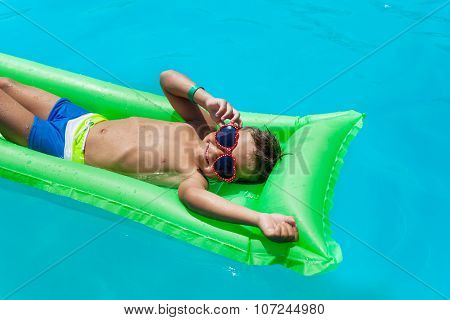 Boy with sunglasses relaxing in swimming pool