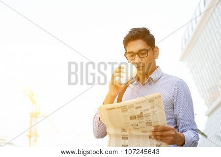 Asian Indian business people drinking coffee and reading newspaper on the way to work place. Handsome male model.