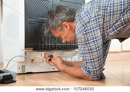 Repairman Repairing Dishwasher With Screwdriver