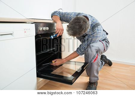 Repairman Examining Oven With Flashlight
