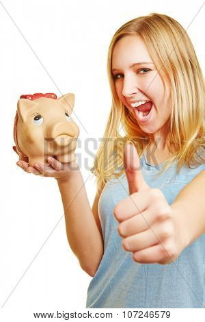 Cheering young blonde woman with piggy bank holding her thumbs up