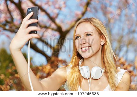 Young woman taking selfie photo with her smartphone in a park