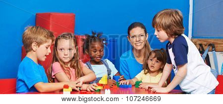 Children playing with building bricks in child care with nursery teacher