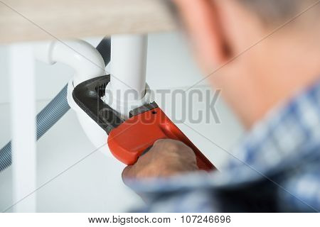Plumber Fixing Sink Pipe In Kitchen