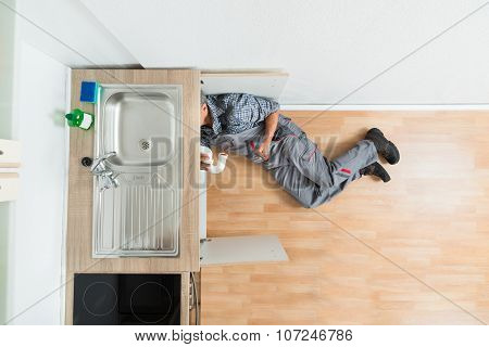 Plumber Working Under Kitchen Sink