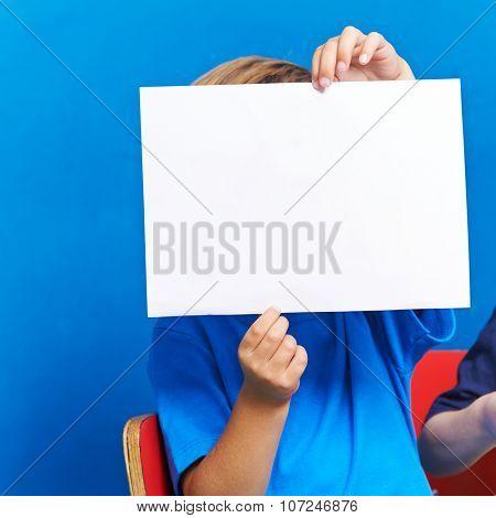 Child showing empty white piece of paper in kindergarten
