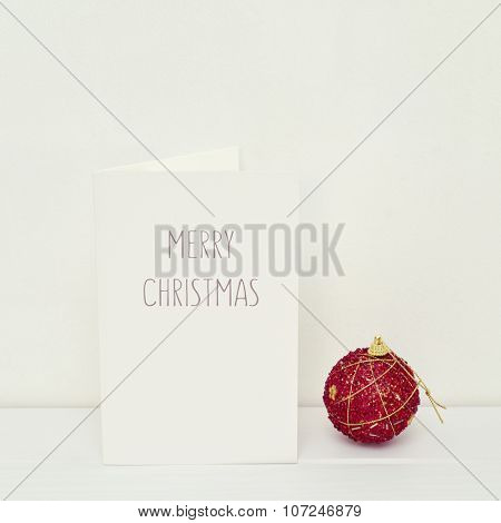 a red Christmas ball and a white greeting card with the text merry christmas in a white scene