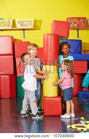 Happy children playing together in a gym of a kindergarten