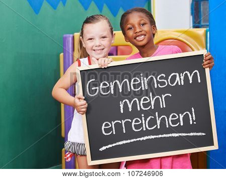 Children holding blackboard saying in German