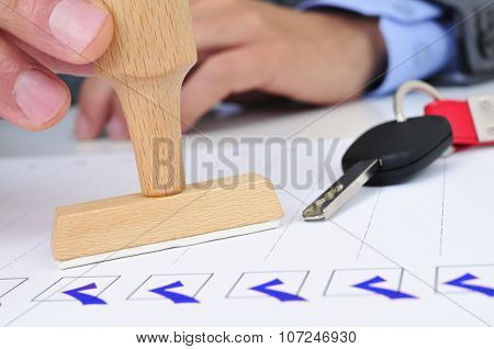 closeup of a young caucasian man in his office with a rubber stamp and a car key on his desk