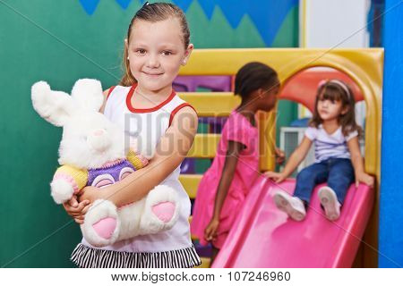 Happy girl holding a stuffed animal in kindergarten